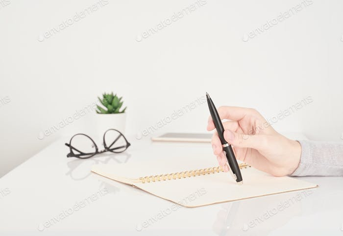 Woman writing on notebook page, office work or study concept, white and gray background