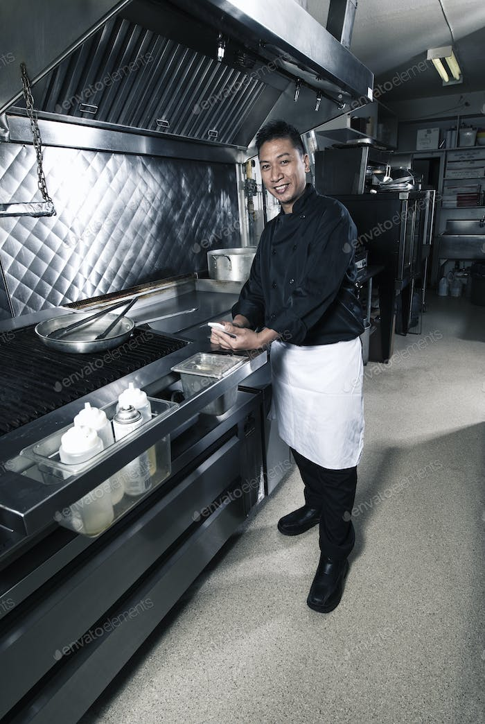 A cook in a commercial restaurant kitchen.