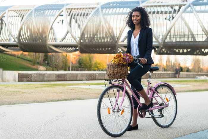Business black woman riding a vintage bicycle in the city