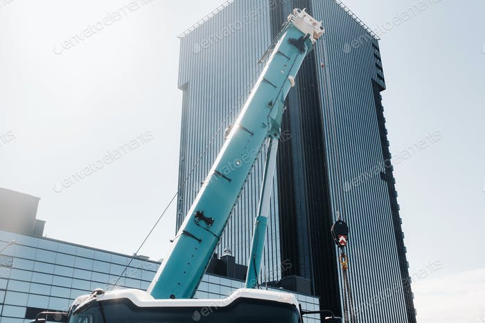 blue crane lifting mechanism with hooks near the glass modern building, crane and hydraulic high