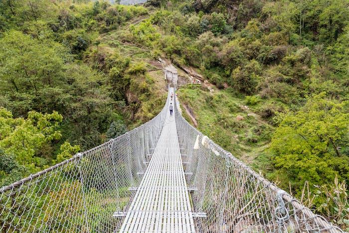 Hikers crossing a long metal suspension bridge in Nepal Annapurn
