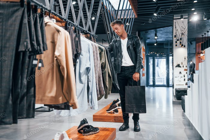 Big choice. Young guy in modern store with new clothes. Elegant expensive wear for men