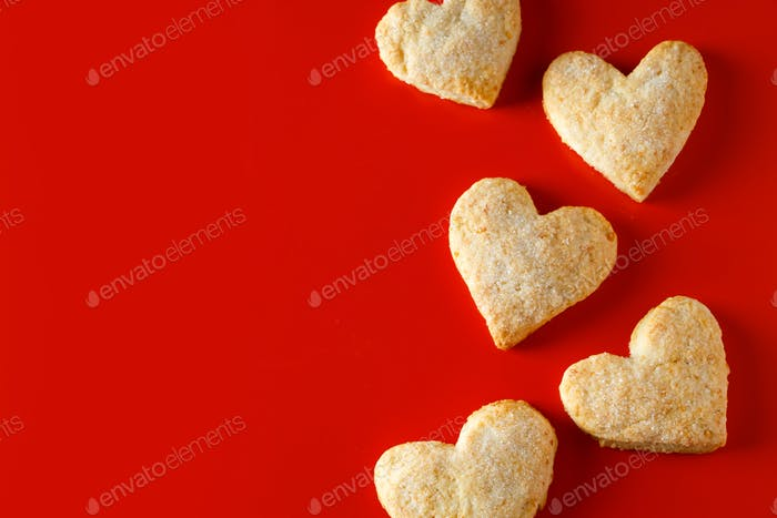 Galletas de azúcar en forma de corazón sobre fondo rojo