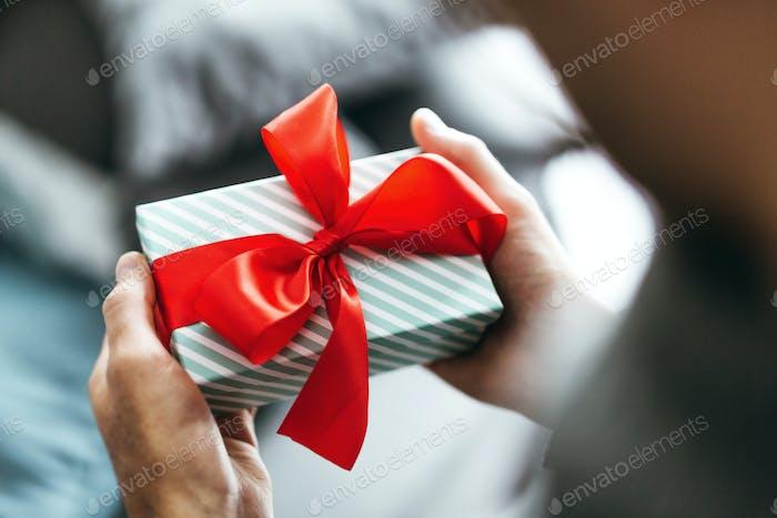 Mann hält Geschenk mit rotem Band