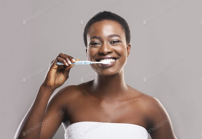 Portrait of beautiful african woman brushing teeth on gray background