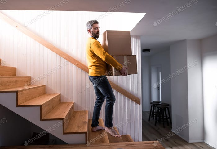 Mature man walking down stairs in house, holding moving boxes.