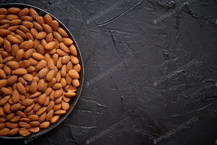 Whole almond nuts in black plate placed on black stone table