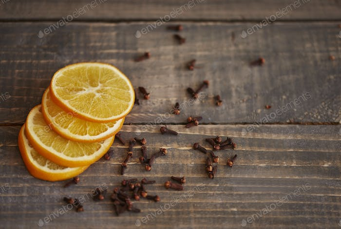 Slices of lemon and cloves on wooden table