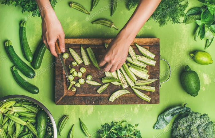 Flat-lay of healthy green vegan cooking ingredients on board