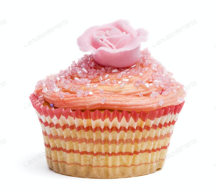 Cupcake with pink flower decoration against white background in front of white background