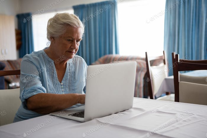 Senior woman using laptop while sitting in nursing home