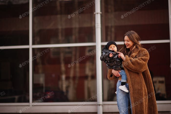 Young mother with child on hands walking down streets.