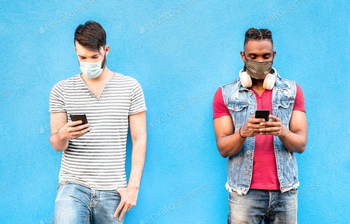 Multiracial male friends with face masks using tracking app with mobile smart phones
