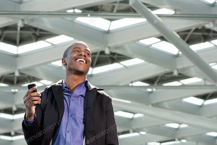 black businessman laughing with cellphone