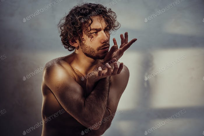 Young caucasian male model is naked and isolated on the grey background