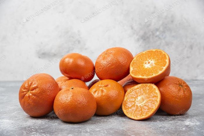 Juicy orange fruits with slices on stone background