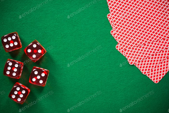 Poker cards and red dices on green casino felt