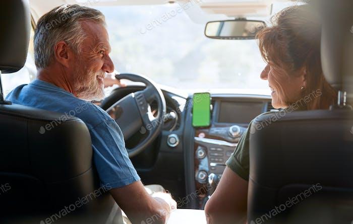 Senior Hispanic Couple On Drive Through Countryside Using Sat Nav On Mobile Phone