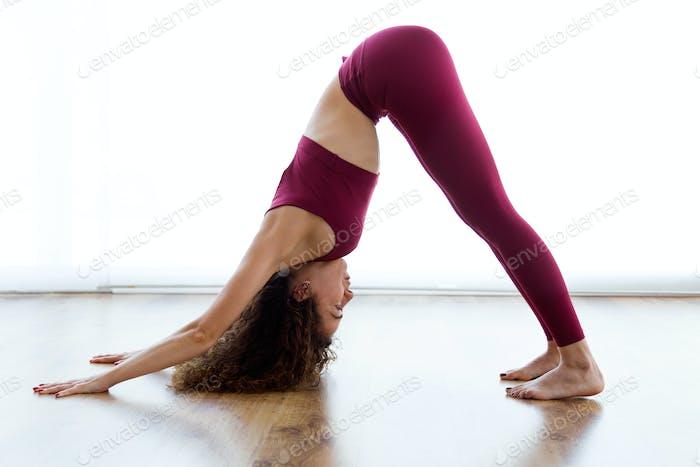 Hübsche junge Frau, die zu Hause Yoga praktiziert. Adho Mukha Svanasana