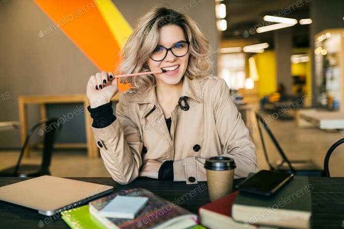 portrait of young pretty woman sitting at table in trench coat working on laptop