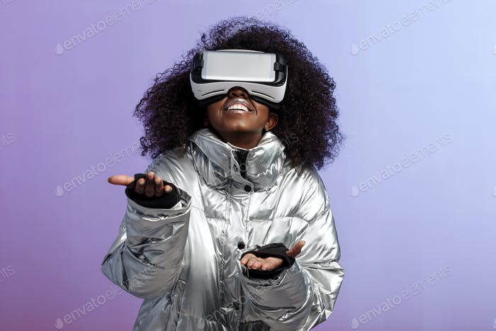 Modern curly brown-haired girl dressed in a silver-colored jacket uses the virtual reality glasses