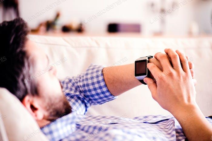 Mann liegend auf dem Sofa zu Hause mit Smartwatch