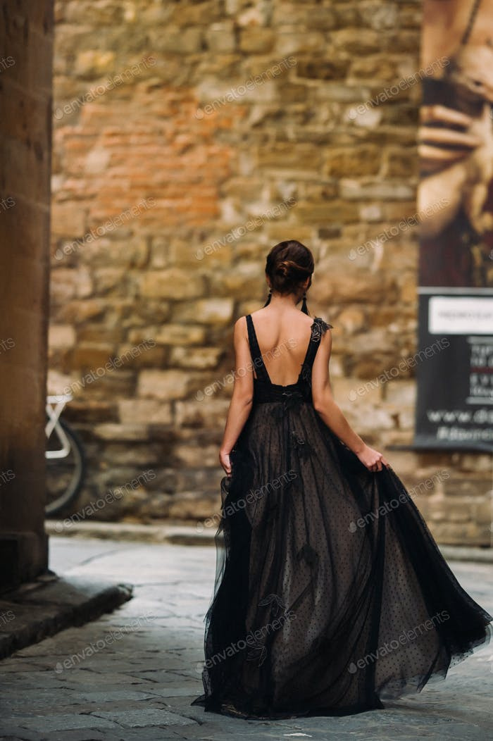 A beautiful stylish bride in a black dress walks through Florence, a Model in a black dress in the