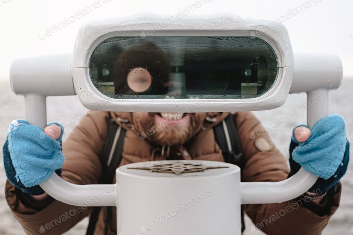 Cheerful man with funny face expression looks at tower viewer like a robot, against the sea