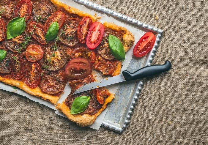 Rustic tomato autumn pie with fresh basil, thyme and tomatoes on