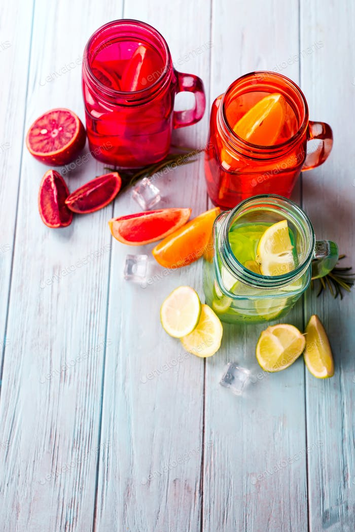 three colored glasses with citrus lemonade and a slice of fruit on a blue background