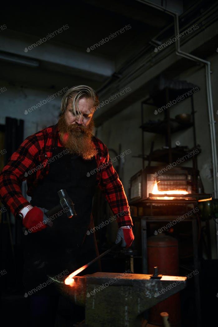 Brutal blacksmith forging wrought iron bar