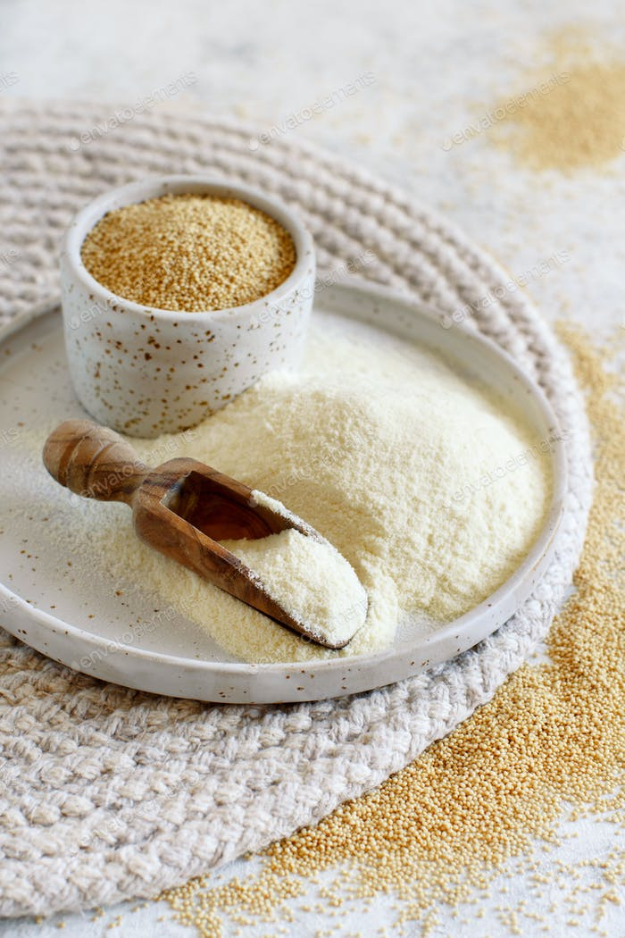 A Plate of raw Amaranth flour with a scoop and a bowl Amaranth seeds