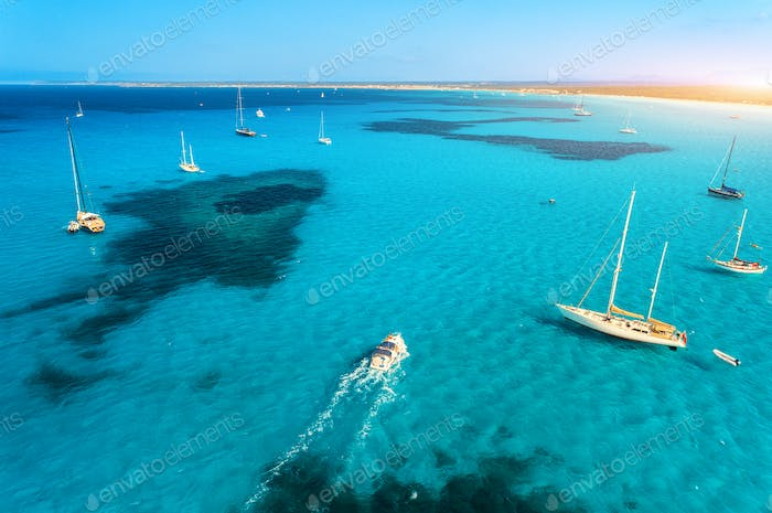 Aerial view of boats and luxury yachts in blue sea at sunny day