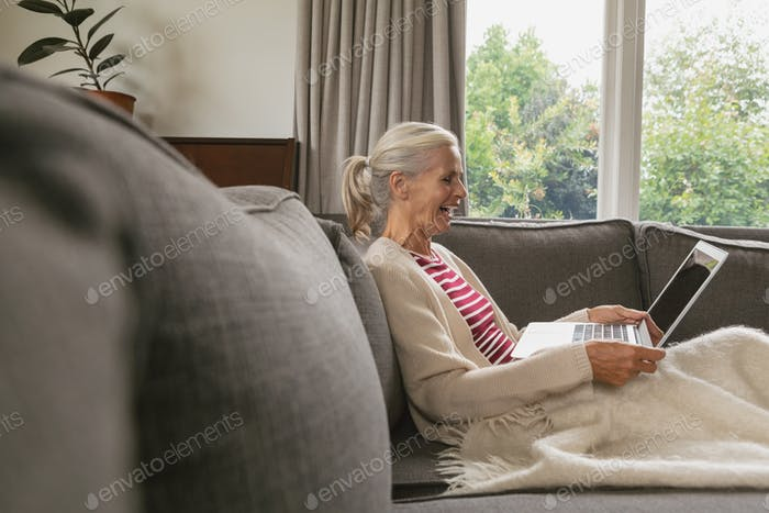 Happy active senior Caucasian woman relaxing on sofa and using laptop in living room