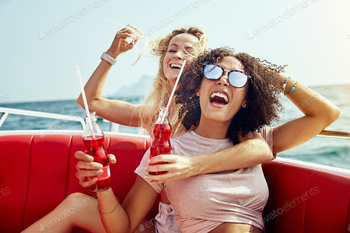 Laughing friends sitting on a boat having drinks during vacation