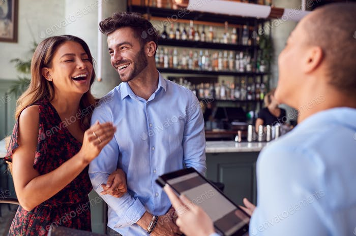 Paar wird von Maitre D mit Digital-Tablet begrüßt, wie sie im Restaurant ankommen