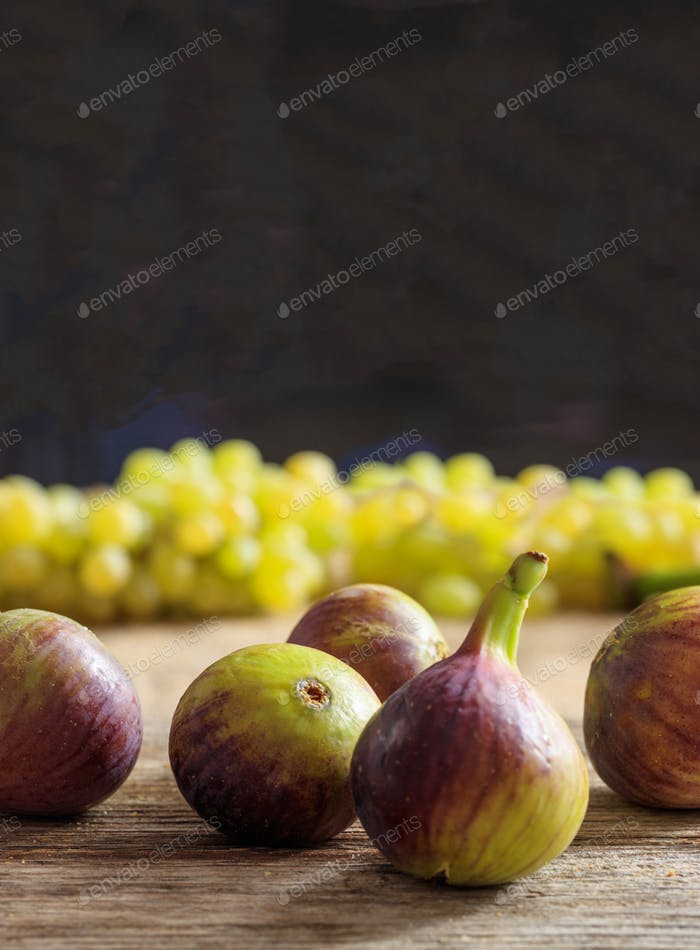 Figs and blur green grapes on wooden table. Black background