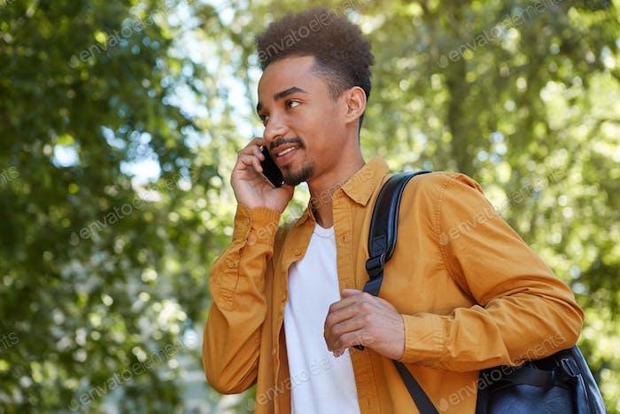 Молодой позитивный афро-американец гуляет по парку и разговаривает по телефону