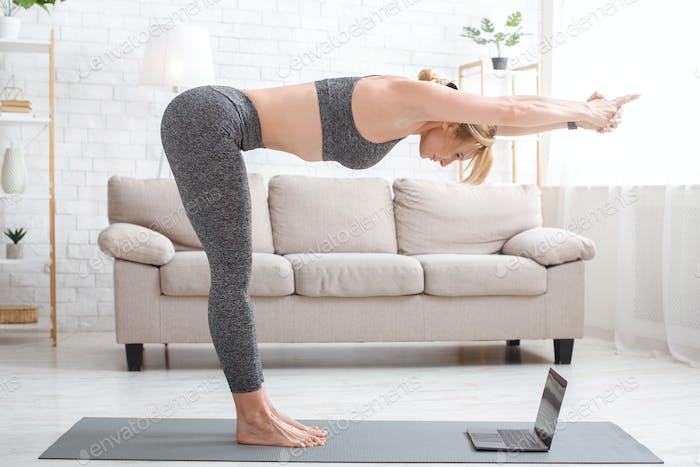 Fitness online zu Hause während der Epidemie. Frau macht Neigung, stehend auf Matte mit Laptop