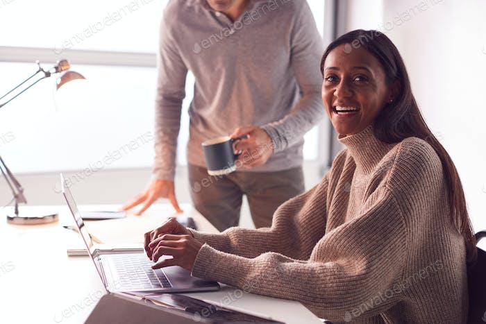 Portrait Of Businesswoman Working On Laptop At Desk As Male Colleague Drinks Coffee In Background