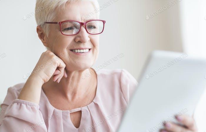 Lächelnd schöne Senior Frau Lesbuch auf digitalem Tablet