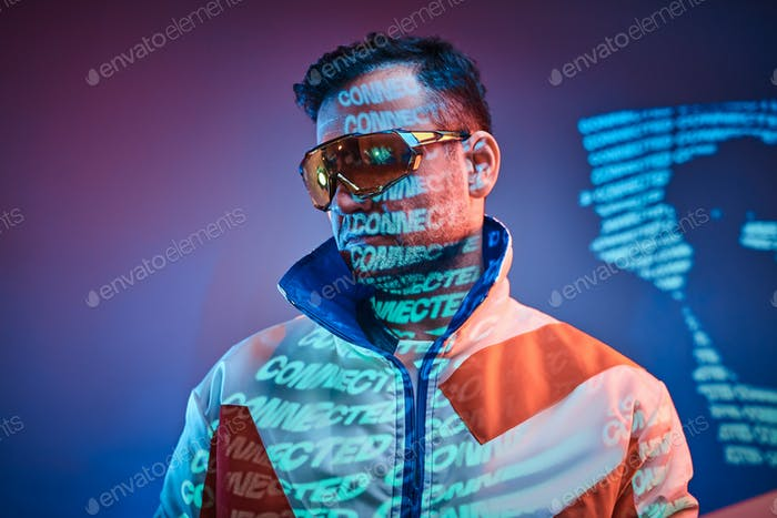Inked attractive male posing in a neon vivid lights of a studio with text, looking cool