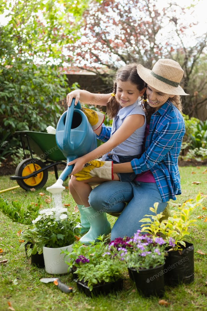 Happy mother teaching daughter to water plants