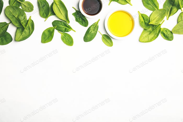 Olive oil, vinegar and fresh spinach, top view