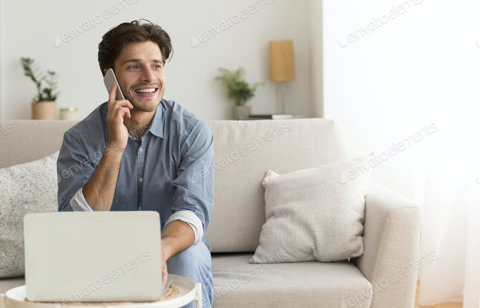 Young Entrepreneur Talking On Phone Sitting At Laptop Indoor