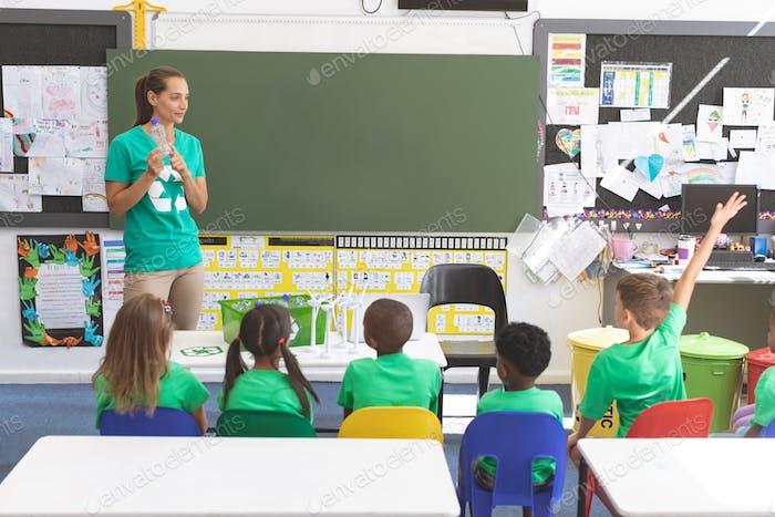 Teacher holding plastic bottle in classroom