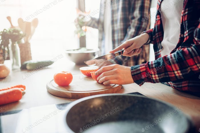 Wife and husband cooking vegetable salad in bowl