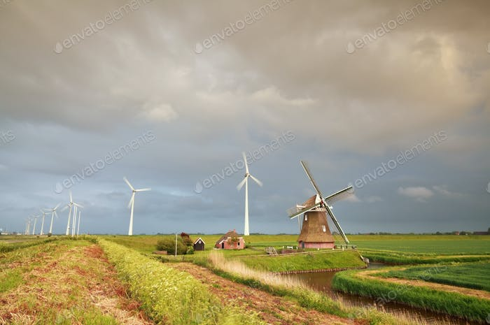 old windmill and turbines at rainy sunset