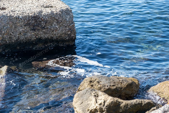 Sea pollution concept. Foam between rocks on the sunny water surface, oil, petroleum, chemicals.