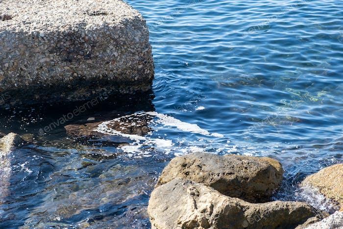 Konzept der Meeresverschmutzung. Schaum zwischen Felsen auf der sonnigen Wasseroberfläche, Öl, Erdöl, Chemikalien.